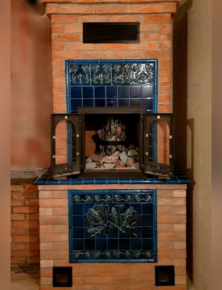 sauna stove is made from handcrafted bricks and is adorned with a mural with ceramic pinecones.