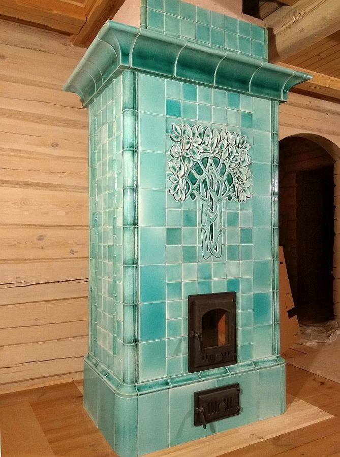 A tiled stove Art Nouveau style in a delicate mint color with a large sculpted snow-covered tree on the front facadeor with a large sculpted snow-covered tree on the front facade