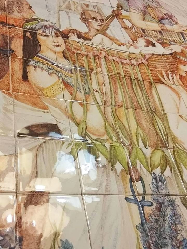 A artistic ceramic tile mural recreating the Finding of Moses by the artist Laurence Alma-Tadema.