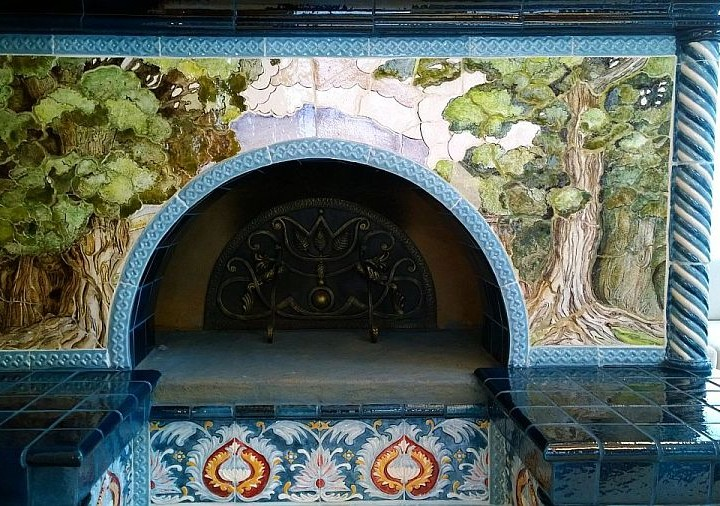 large Russian tiled stove with a stove bed is covered with tiles and ceramic panels with art murals
