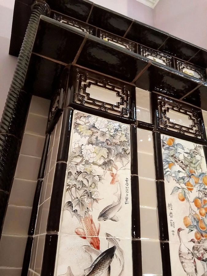 A chinoiserie tiled fireplace with picturesque murals in the huaniao genre (flowers and birds)