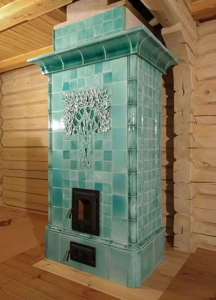 A tiled stove Art Nouveau style in a delicate mint color with a large sculpted snow-covered tree on the front facade