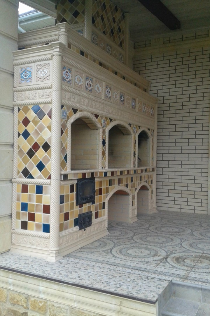 A outdoor kitchen tiled oven in Neo-Russian-style with large rump relief tiles and multi-colored majolica